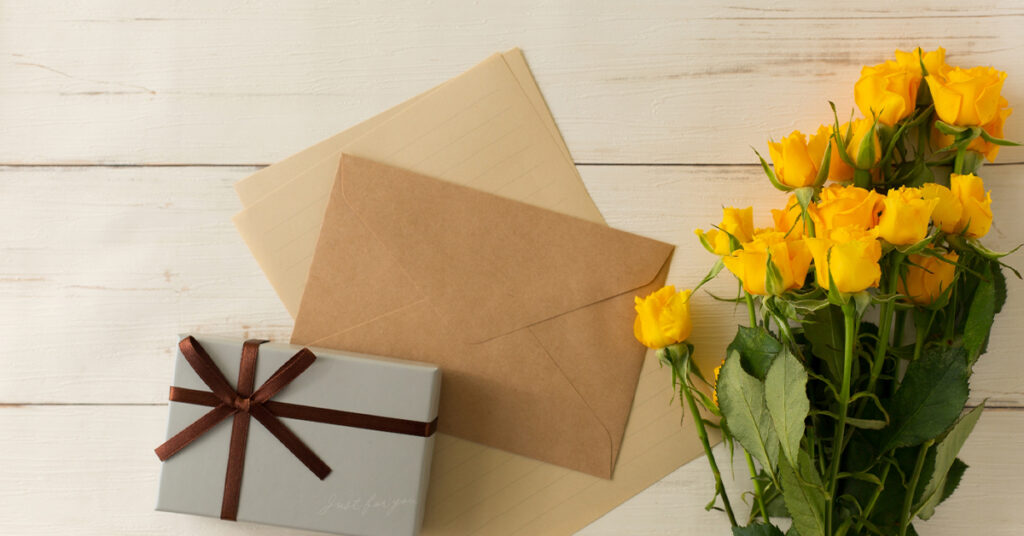 春の新生活応援ギフト プレゼントボックスと茶封筒と手紙のセットと黄色いバラの花束